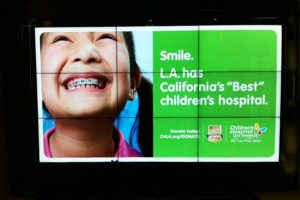 Ad for Children's Hospital with little girl showing her brasse